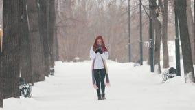 日霜1月天然公园多雪的结构树冬天 有明亮的红色头发的一名妇女谈话在电话 股票视频