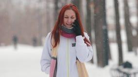 日霜1月天然公园多雪的结构树冬天 有明亮的红色头发的一名微笑的妇女谈话在电话 股票视频