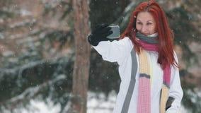 日霜1月天然公园多雪的结构树冬天 有明亮的红色头发身分在多雪的树前面和采取的selfie一名妇女 降雪 股票录像