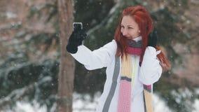 日霜1月天然公园多雪的结构树冬天 有明亮的红色头发身分在多雪的树前面和采取的selfie一名妇女 影视素材