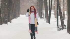 日霜1月天然公园多雪的结构树冬天 有明亮的红色头发身分的一名妇女在边路 跳跃和摇她的手 股票录像