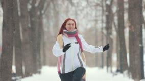 日霜1月天然公园多雪的结构树冬天 有跳离照相机较近的明亮的红色头发的一名妇女 股票视频