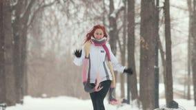 日霜1月天然公园多雪的结构树冬天 有跳离照相机较近的明亮的红色头发的一名微笑的妇女 股票录像