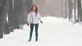 日霜1月天然公园多雪的结构树冬天 有明亮的红色头发身分的一名妇女在边路,做雪球和今后投掷它 股票录像