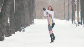 日霜1月天然公园多雪的结构树冬天 有明亮的红色头发身分的一名快乐的妇女在边路,做雪球和今后投掷它 影视素材