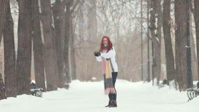 日霜1月天然公园多雪的结构树冬天 有明亮的红色头发身分的一名快乐的微笑的妇女在边路,做雪球和投掷它 股票录像