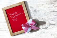 日s华伦泰 一个框架与题字愉快的华伦泰` s天和有一把桃红色弓的一个礼物盒 免版税图库摄影