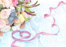 日s华伦泰 华伦泰礼物 在心脏花形状和花束的缎丝带在蓝色木背景的 免版税库存图片