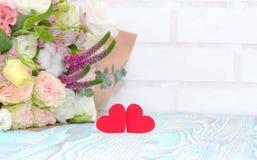 日s华伦泰 华伦泰礼物 花红色心脏和花束在蓝色木背景的 美好的华伦泰卡片艺术设计 免版税库存图片
