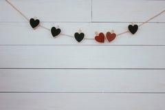 日s华伦泰 在自然绳子的红色和黑心脏hangin 木白色背景 减速火箭的样式 免版税库存图片