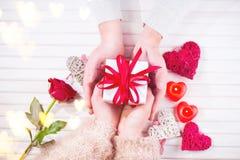 日s华伦泰 年轻夫妇递拿着在白色木背景的礼物盒 概念亲吻妇女的爱人 免版税库存图片