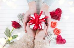 日s华伦泰 年轻夫妇递拿着在白色木背景的礼物盒 库存图片