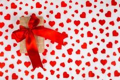 日s华伦泰 提出作为在白皮书的一条红色丝带与红色心脏 图库摄影