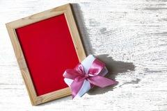 日s华伦泰 文本和礼物盒的空的框架有一把桃红色弓的 概念:华伦泰` s天 库存照片
