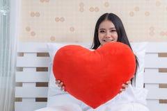 日s华伦泰 有一件礼物的美丽的微笑的妇女以心脏的形式在他的手上 库存照片