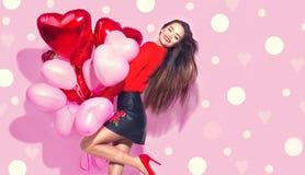 日s华伦泰 有获得五颜六色的气球的秀丽女孩乐趣 免版税库存图片