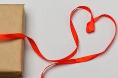 日s华伦泰 礼物盒在灰色背景栓与一条红色丝带,红色丝带被放置以心脏的形式,在a旁边 库存照片