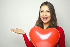 日s华伦泰 穿红色礼服和拿着一个红色心脏气球的美丽的少妇显示您的产品或文本在丝毫 库存照片