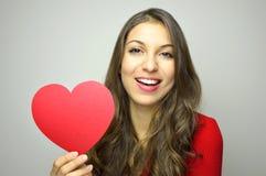 日s华伦泰 穿红色礼服和拿着在灰色背景的美丽的少妇纸红色心脏 在红色玫瑰色华伦泰白色的概念重点 免版税库存照片