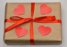 日s华伦泰 在灰色背景的礼物盒在卡拉服特褐色包裹栓与一条红色丝带和在上面是四被雕刻的红色的 免版税库存图片