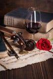 旧书、小提琴纸卷和红色玫瑰 库存图片