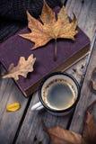 旧书、被编织的毛线衣有秋叶的和咖啡杯 库存图片