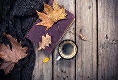 旧书、被编织的毛线衣有秋叶的和咖啡杯 免版税库存图片