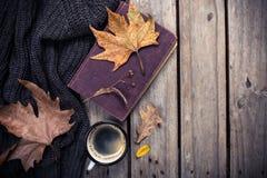 旧书、被编织的毛线衣有秋叶的和咖啡杯 免版税库存照片