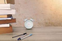 旧书、课本、蓝色经典闹钟和笔在葡萄酒木桌上在葡萄酒难看的东西混凝土墙背景 库存照片