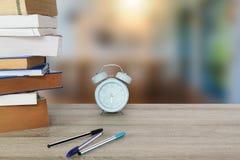 旧书、课本、蓝色经典闹钟和笔在葡萄酒木桌上在被弄脏的室背景 库存图片