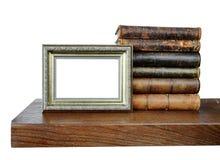 旧书和一个古色古香的照片框架 免版税库存照片