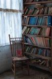 旧书和一把椅子在一个被放弃的校舍书架 库存照片