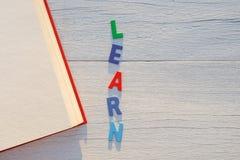 旧书和学会五颜六色的字母表词 在白色的顶视图求爱 免版税图库摄影