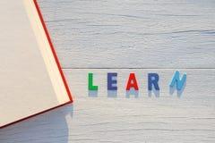 旧书和学会五颜六色的字母表词 在白色的顶视图求爱 免版税库存图片