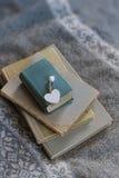 旧书和木心脏谎言在毛线衣 冷口气 软的焦点,背景 免版税库存图片