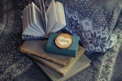旧书和木心脏谎言在毛线衣 温暖的口气 背景 软绵绵地集中 免版税库存图片
