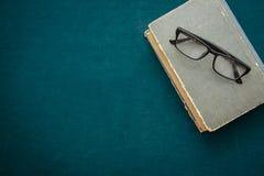 旧书和玻璃在桌上 库存图片