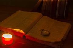 旧书在烛光的图书馆里 圣经在桌上 老怀表 3d变老被回报的例证中间名 占卜 预测 库存图片