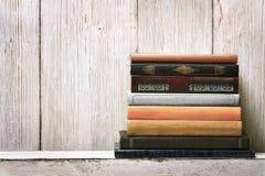 旧书架子空白脊椎,在木纹理的空的捆绑堆 免版税库存照片