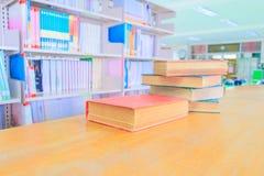 旧书红绿色 堆是在木桌上的内部图书馆学校和模糊的书架背景 库存照片
