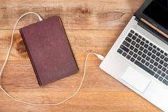 旧书连接的膝上型计算机,演变书概念 免版税库存图片