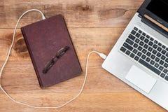 旧书连接的膝上型计算机,演变书概念 免版税图库摄影