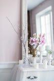 破旧的别致的家庭设计 与一个蜡烛的美丽的装饰桌,在镜子前面的花 免版税库存图片