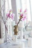 破旧的别致的家庭设计 与一个蜡烛的美丽的装饰桌,在镜子前面的花 库存照片
