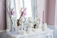 破旧的别致的家庭设计 与一个蜡烛的美丽的装饰桌,在镜子前面的花 库存图片