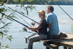 更旧的夫妇坐浮船和钓鱼 库存图片
