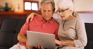 更旧的夫妇特写镜头使用膝上型计算机的在家 免版税库存图片