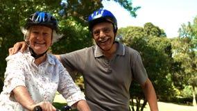 更旧的夫妇骑马自行车在公园 股票视频