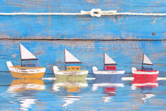 破旧的玩具小船连续在蓝色背景-在海holi 免版税库存照片