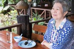 更旧的senoir等待的食物 坐在稀土的愉快的年长妇女 免版税库存照片